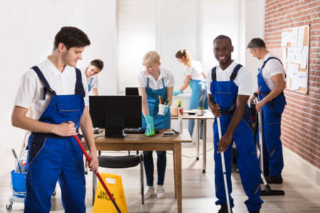 office cleanup: Group Of Diverse Janitors In Uniform Cleaning The Office With Cleaning Equipments