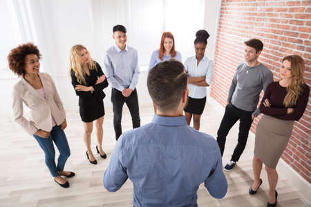 large group of business people: Rear View Of Manager Having Conversation With His Business Colleagues In The Office Stock Photo