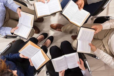 Podwyższony widok ludzi siedzących na krześle w kręgu czytających książki
