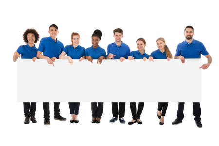 Group Of Happy Janitors Holding Long Billboard Over White Background