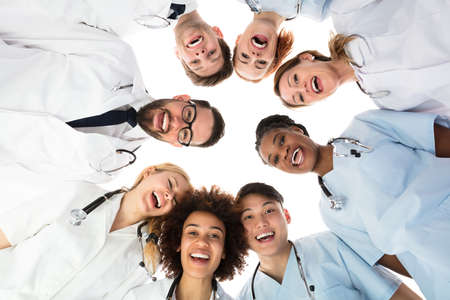 Low Angle View Of Smiling Medical Team Standing Against White Background Stockfoto