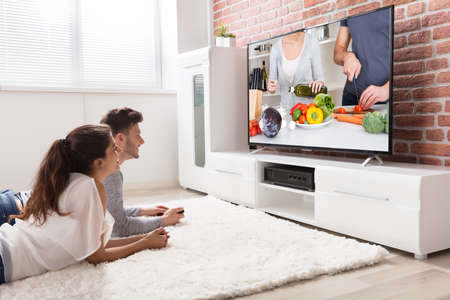 Happy Young Couple Sitting On Sofa Watching Recipe On Television At Home photo
