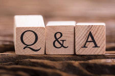 Nahaufnahme des schwarzen Q & A Text auf hölzernem Block