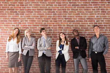 Diverse Group Of Businesspeople Standing Near The Brick Wall Looking Up Stock Photo