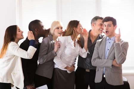 Colegas de negocios chismes secretos susurrando a un sorprendido hombre con escándalo de boca abierta