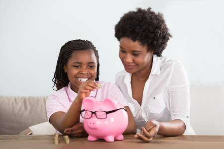 집에서 핑크 돼지 저금통에 동전을 삽입하는 그녀의 어머니와 함께 앉아있는 아프리카 여자