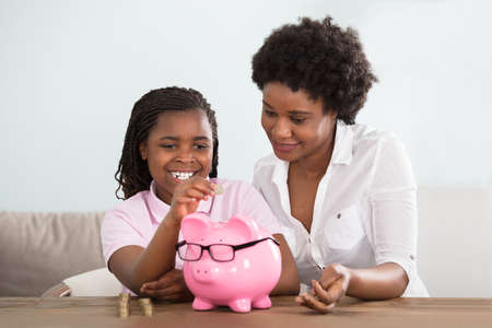 An African Girl Sitting With Her Mother Inserting Coins In Pink Piggy Bank At Home Stockfoto