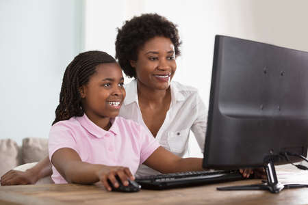 An African Mother And Daughter Looking At Computer On Table At Home