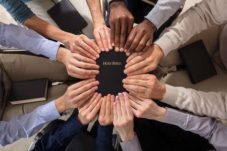 Vista aérea de las manos sosteniendo la Santa Biblia