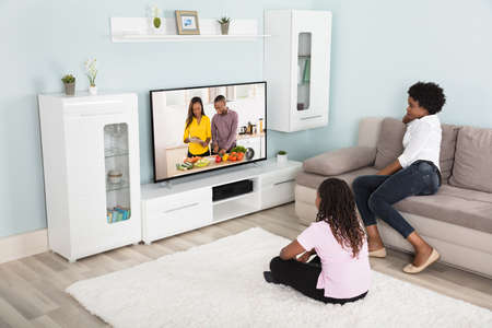 Mother And Daughter Watching Enjoying Watching Television At Home Banque d'images