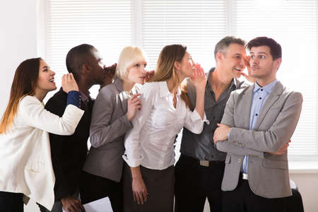 口を大きく開けて驚いてショックを受けた男に秘密のゴシップをささやきビジネス同僚