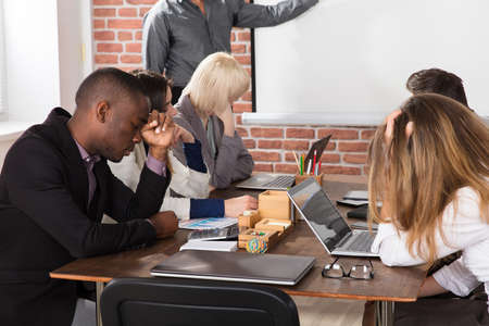 Diverse tired young business people bored during meeting in office