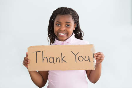 Close-up Of A Smiling African Girl Holding Thank You Sign Against White Background