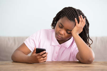 Close-up Of An African Bored Girl Looking At Cell Phone Redakční