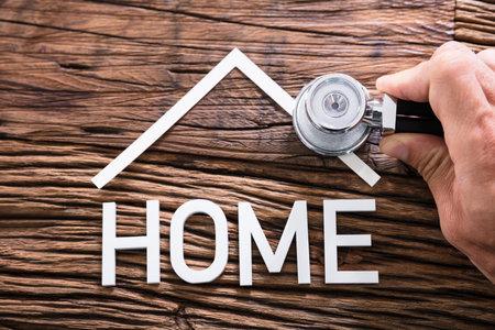 Nahaufnahme von Person Hand Holding Stethoscope Near Home Text auf Holztisch Standard-Bild - 81904170