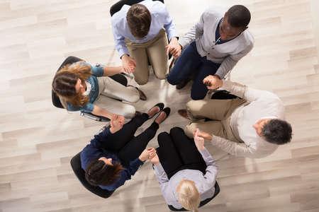 Veduta aerea di persone sedute sulla sedia nel cerchio che si sostengono a vicenda