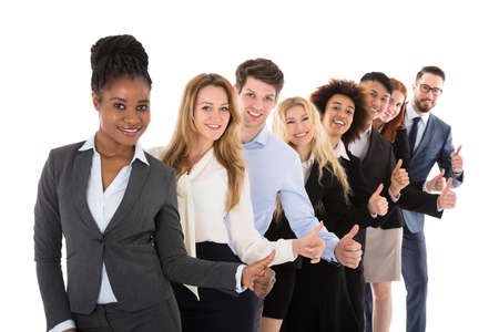 large group of business people: Confident Young Businesspeople Gesturing Thumbs Up Over White Background