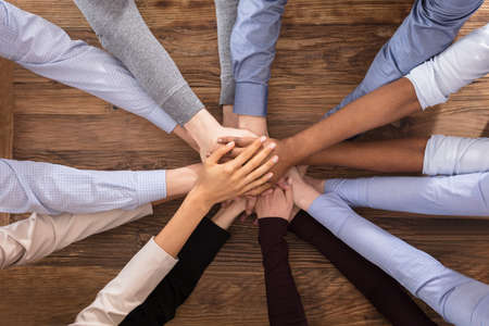 large group of business people: High Angle View Of Multiracial Businesspeople Stacking Their Hands