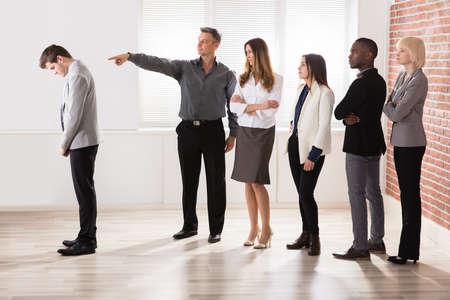 Älterer Geschäftsmann, der auf seinen Kollegen im Büro zeigt