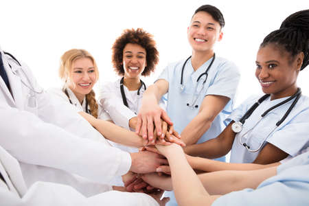 Group Of Happy Doctors Stacking Their Hands Against White Background Stock Photo