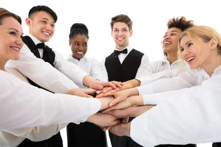 Smiling Young Restaurant Staff Stacking Hands Over White Background