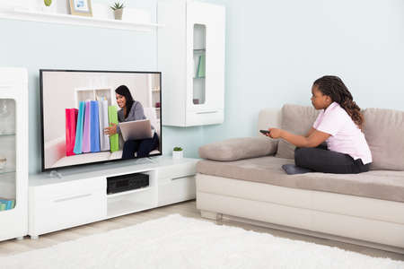 Girl sitting on couch using remote control while watching television at home photo