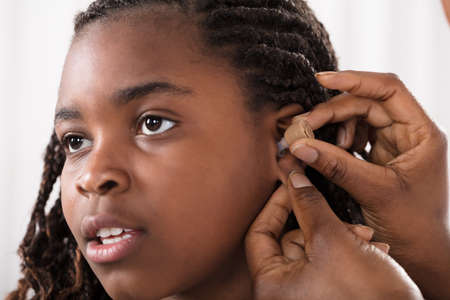 Close-up Of A Doctor Putting Hearing Aid In Patients Ear