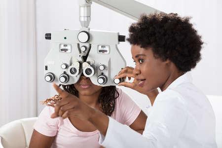 Mujer africana optometrista hacer pruebas de vista para el paciente en el hospital