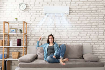 Happy Young Woman Holding Remote Control Relaxing Under The Air Conditioner Stockfoto