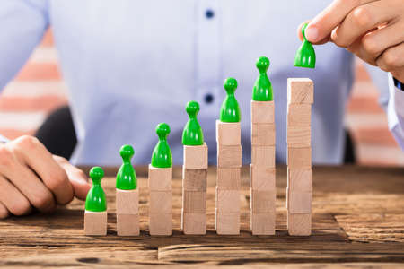 Businessman Arranging The Green Figures On Increasing Wooden Block Stack Stock Photo