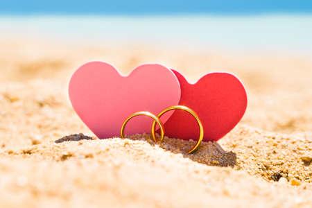 夏のビーチで砂の上の黄金のリングと 2 つのハートの形 写真素材
