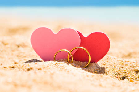 Two Heart Shapes With Golden Rings On Sand At Beach In Summer