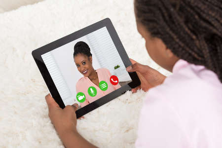 Close-up Of A Girl Video Conferencing With Her Mother On Tablet
