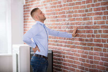 Young Man Leaning On Wall Touching His Back In Pain