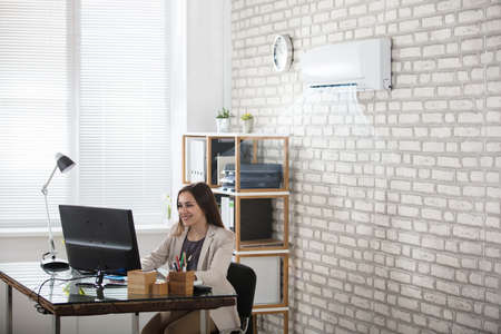 cool gadget: Happy Young Businesswoman Working In Office With Air Conditioning Stock Photo