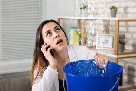 Worried Woman Calling Plumber While Collecting Water Droplets Leaking From Ceiling At Home