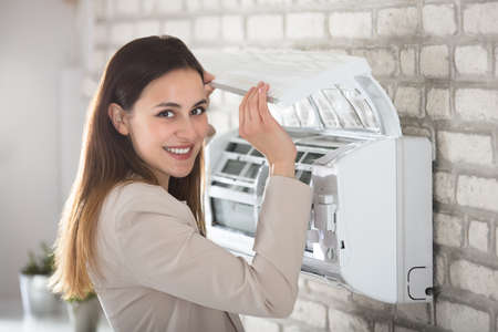 Young Woman Opening Air Conditioner Attached On Wall