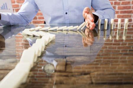 Nahaufnahme eines Geschäftsmannes Stopping Dominoes Row vom Zerbröckeln über dem Glasschreibtisch Standard-Bild - 81707734