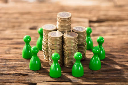 Stack Of Coins Surrounded With Green Figures On Wooden Desk Stock Photo
