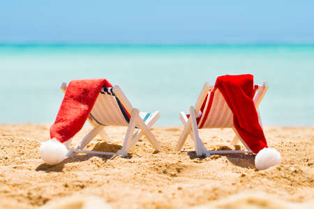 Two Miniature Deck Chairs With Santa Hats Kept Near The Coast At Beach