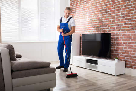 Smiling Male Janitor In Uniform Sweeping Floor With Broom At Home Stock Photo - 81655529