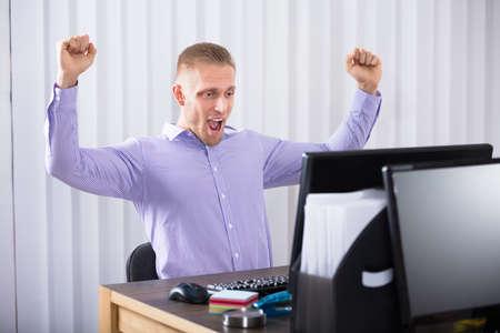 Succesvolle Jonge Zakenman Die Zijn Handen In Het Bureau Opheffen