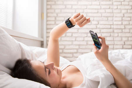 Close-up Of A Young Woman Lying On Bed Synchronizing Smart Watch With Cell Phone Stok Fotoğraf
