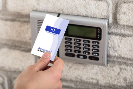 A Persons Hand Holding Access Card To Lock And Unlock Door
