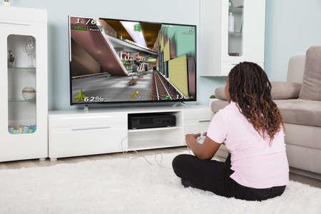 ビデオ ゲームを家庭でアフリカの女の子の後姿 写真素材
