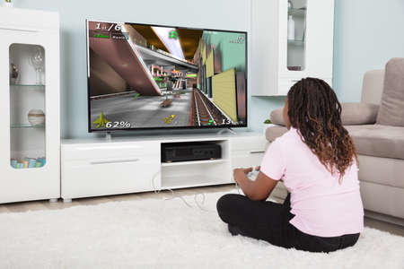 Rear View Of An African Girl Playing Video Games At Home Banque d'images