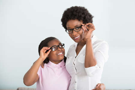 Portrait Of A Smiling Daughter And Mother With Eyeglasses Against White Background Stock Photo