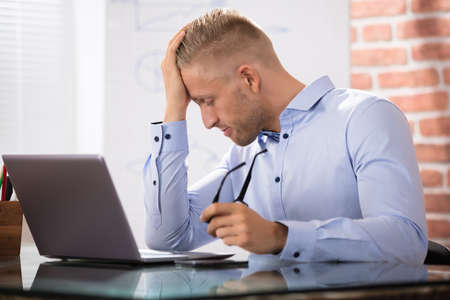 headaches: Close-up Of Depressed Businessman Looking At Laptop Over The Desk In Office