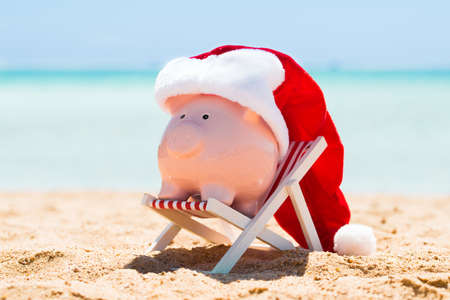 A Pink Piggy Bank With Santa Hat Kept On The Deck Chair At Beach Reklamní fotografie - 81655573
