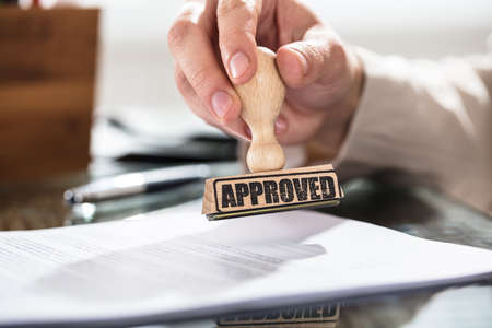 Close-up Of A Person Holding Approved Stamp On Document Over The Desk In Office Stock Photo